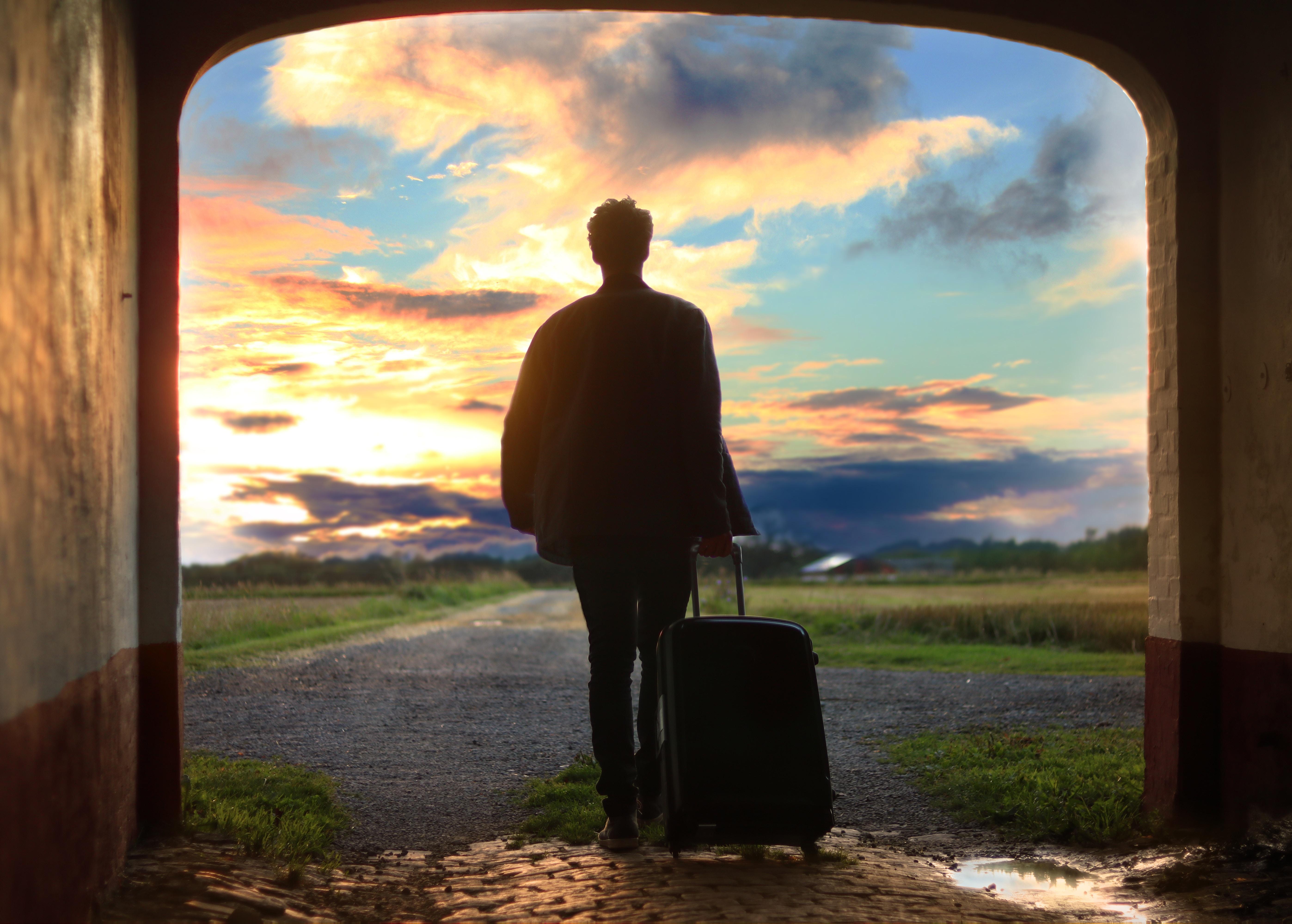 スーツケースを持ち旅に出かける男
