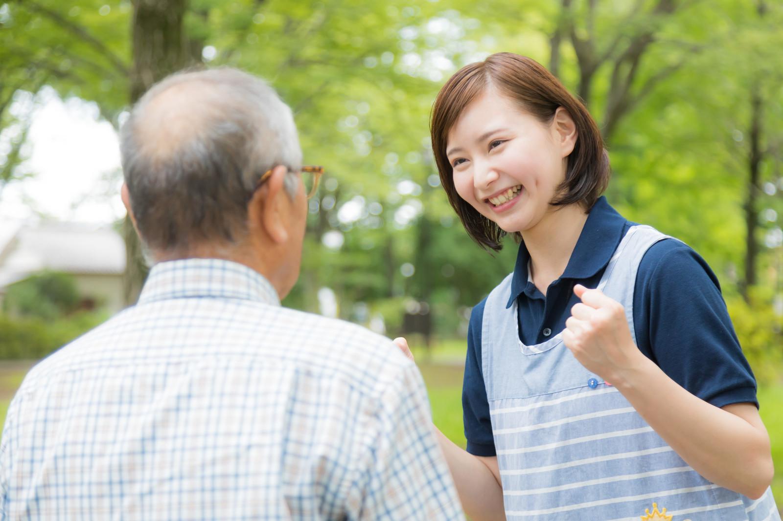 爺さんと会話する介護士